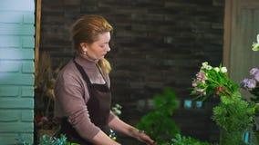 Frauenflorist Tannenzweig von den Kiefernnadeln reinigen, um den Blumenstrauß vorzubereiten stock footage
