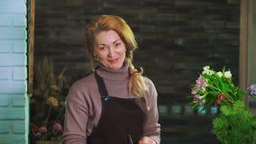 Frauenflorist Tannenzweig von den Kiefernnadeln reinigen, um den Blumenstrauß vorzubereiten Betrachten Sie die Kamera stock footage