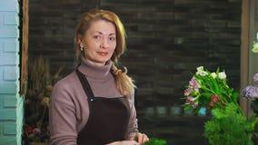 Frauenflorist Tannenzweig von den Kiefernnadeln reinigen, um den Blumenstrauß vorzubereiten Betrachten Sie die Kamera stock video