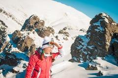 Frauenforscherskifahrer in den Bergen mit schneebedecktem felsigem Hintergrund Stockbilder