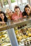 Frauenfreunde, die Kuchen im Kaffee betrachten Lizenzfreie Stockfotos