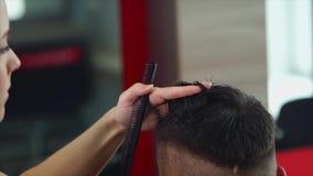Frauenfriseur, der dem jungen Mann Haarschnitt macht Sie unter Verwendung der Scheren und des Kammes stock video
