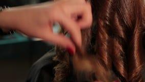 Frauenfriseur, der Locken am roten Haar macht Frau in einem Schönheitssalon stock video