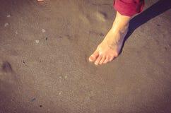 Frauenfuß auf nassem Sand Stockfotos