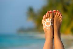 Frauenfuß mit sonnen-förmiger Sonnencreme im tropischen Strand conce Lizenzfreie Stockfotos