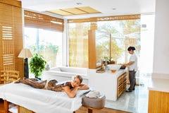Frauenfuß im Wasser Badekurort - 7 Frauen-Masken-Schönheits-Salon Haut-Therapie Stockfotografie