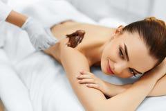 Frauenfuß im Wasser Badekurortschönheitsbehandlung Kosmetische Schablone Zutreffen des transparenten Lacks Stockfotos