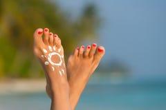 Frauenfuß mit sonnen-förmiger Sonnencreme im tropischen Strand conce Stockfotografie