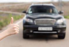 Frauengeben Daumen oben, wie sie per Anhalter fahrend steht Lizenzfreies Stockfoto