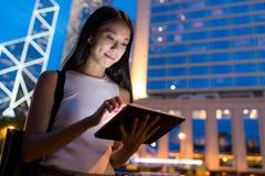 Frauengebrauch der digitalen Tablette in der Stadt Stockfotos