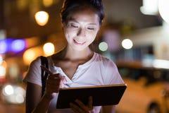 Frauengebrauch der digitalen Tablette nachts in der Stadt Lizenzfreie Stockfotografie