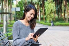 Frauengebrauch der digitalen Tablette am Park Stockfotos