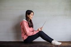 Frauengebrauch der digitalen Tablette zu Hause Lizenzfreie Stockfotos