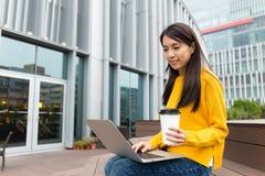 Frauengebrauch der Laptop-Computers mit Kaffeetasse Lizenzfreies Stockfoto