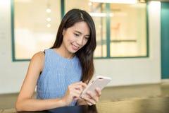 Frauengebrauch des Mobiltelefons an der Kaffeestube Lizenzfreie Stockfotografie
