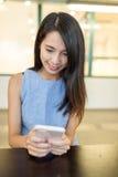 Frauengebrauch von Handy an der Kaffeestube Lizenzfreie Stockfotos