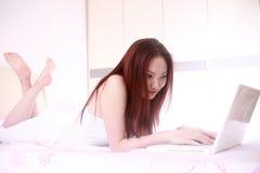 Frauengebrauchlaptop auf Bett Lizenzfreies Stockfoto