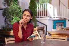 Frauengefühl beim Warten auf ihre Bestellung im Café gebohrt Lizenzfreie Stockfotos