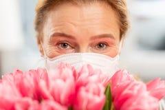 Frauengefühl zufriedengestellt, nachdem Tulpen aber in der Maske gerochen worden sind lizenzfreie stockfotografie