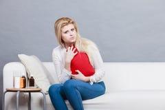 Frauengefühls-Magenklammern, die auf cofa sitzen Lizenzfreies Stockfoto