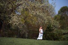 Frauengehen, -betrieb des jungen Reisenden genie?t das schwangere, herum drehend und ihre Freizeitfreizeit in einem Park mit lizenzfreies stockfoto
