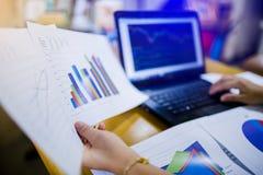 Frauengeldmarktanalytiker, der an Laptop beim Sitzen am Holztisch arbeitet lizenzfreie stockfotos