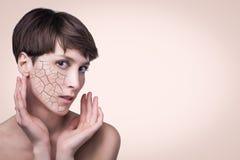 Frauengesicht bedeckt mit gebrochenem Erdbeschaffenheitssymbol der trockenen Haut stockfotografie
