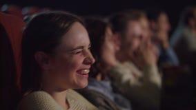 Frauengesicht, das lustigen Film am Kino aufpasst Aufpassender Komödienfilm der Kinoleute stock video footage