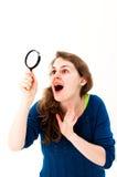 Frauengesicht denken einen Blick herauf und mit Lupe Lizenzfreie Stockfotos