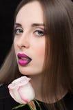 Frauengesicht mit den lila Lippen und Rose Flower Lizenzfreie Stockbilder