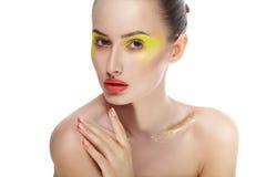 Frauengesicht mit hellem gelbem Make-up und Maniküre stockbilder