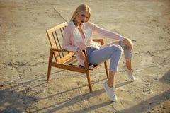 Frauengesichtshautpflege Porträtfrauengesicht in Ihrer advertisnent sexy Frau sitzen auf Holzstuhl auf Betondecke Lizenzfreies Stockbild