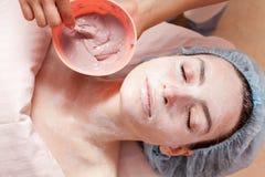 Frauengesichtsschablonenanwendungs-Schönheitsbehandlung Lizenzfreie Stockfotografie