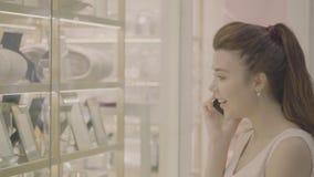 Frauengespräch am Telefon und Blick auf Schaukasten im Mall stock video footage