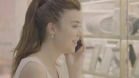 Frauengespräch am Telefon und Blick auf Schaukasten im Mall stock footage