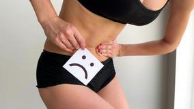 Frauengesundheit Weiblicher K?rper-Holding-traurige L?cheln-Karte nahe Magen stock footage