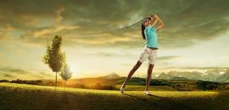 Frauengolfspieler, der den Ball auf der Hintergrundlandschaft schlägt Lizenzfreies Stockfoto