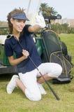 Frauengolfspieler, der einen Golfball anhält Stockfotografie