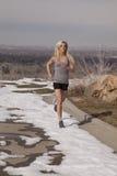Frauengrau gelaufen in Schnee Stockfotos