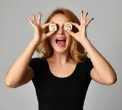 Frauengriff-Sushirollen in den lächelnden Händen und in den nahen Augen auf einem hellgrauen lizenzfreies stockbild