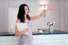 Frauengrundst?cksmakler schl?gt vor, Ebene oder Wohnung zu besuchen Mittel zeigt mit der Hand etwas Wohnung stockfoto