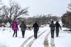 Frauengruppe auf der Rückseite, die einen Spaziergang im Schnee macht lizenzfreie stockbilder