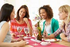 Frauengruppe, die um die Tabelle isst Nachtisch sitzt lizenzfreie stockfotografie