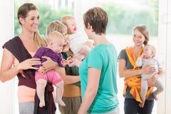 Frauengruppe, die wie man Babyriemen für Mutterkind lernt, benutzt Lizenzfreie Stockfotos