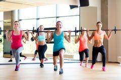 Frauengruppe mit Barbells in der Turnhalle Stockfoto