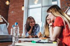 Frauengruppearbeitssitzen am Schreibtisch im Büro lizenzfreie stockfotos