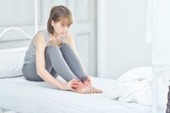 Frauenhändchenhalten auf dem Knöchel lizenzfreie stockbilder