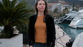 Frauenhändchenhalten in den Jeans und in den Wegen entlang dem Strand mit Yachten stock video