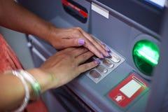 Frauenhände auf ATM-Maschine Stockbild