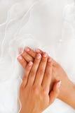 Frauenhände auf einem weißen Kleidhintergrund Stockfoto